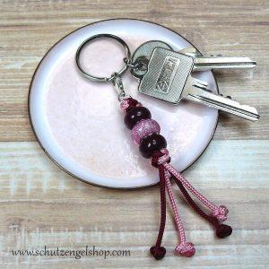 Schlüsselanhänger aus Paracord und Perlen in rosa und bordeaux