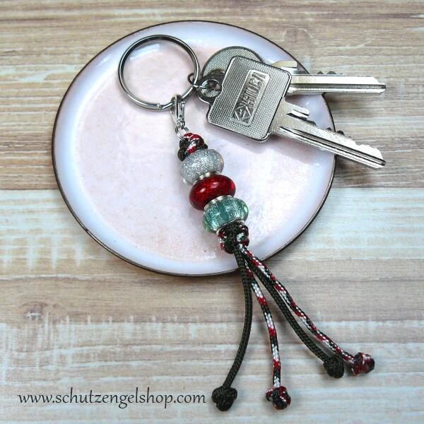Schlüsselanhänger aus Paracord in dunkelgrün und Perlen in weiß, rot und hellgrün